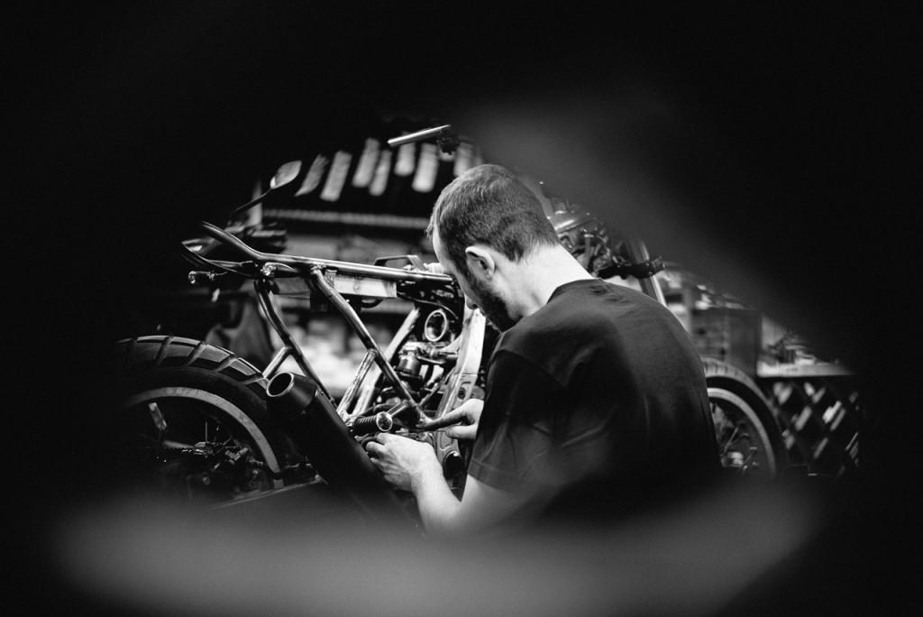 Vue de dos Isidore Delgrosso travaillant sur une moto - Atelier Mécaservices92